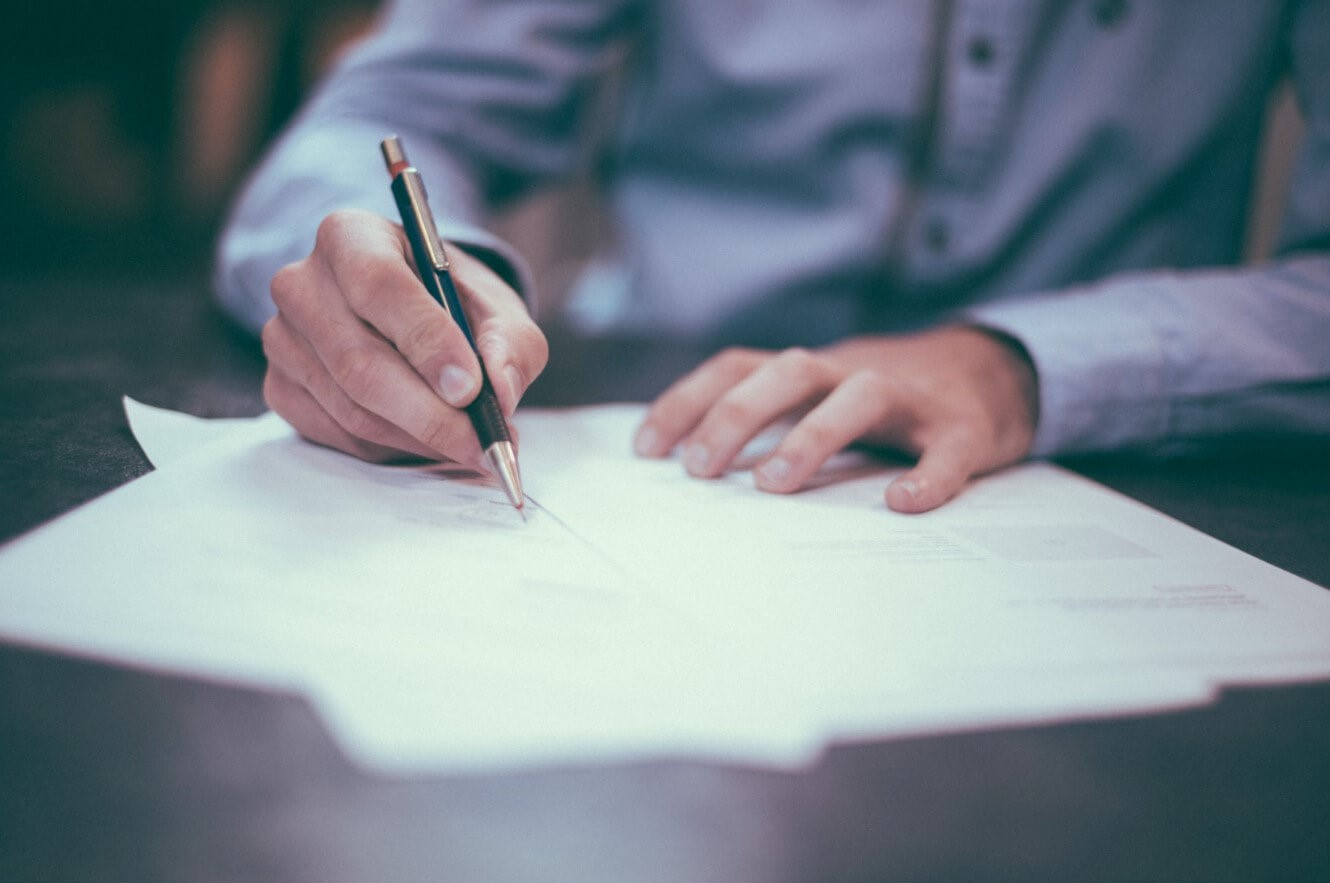 Man signing papers on desk